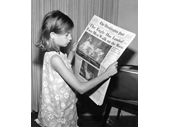 76 - A girl reads the headlines about man walking on the Moon