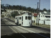 29 - A tram heads along Wynnum Road with the Balmoral cemetery in the background